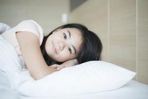 ベッドで横になっている女の子の写真素材 [FYI04315918]