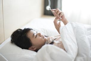 ベッドで横になってスマホを見ている女の子の写真素材 [FYI04315922]