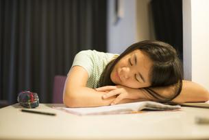 机の上で眠っている女の子の写真素材 [FYI04315923]