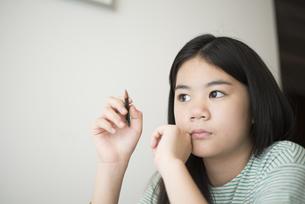 鉛筆を持って考えている女の子の写真素材 [FYI04315924]