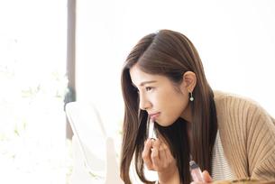 鏡を見ながら化粧をしている女性の写真素材 [FYI04315943]