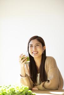 グリーンスムージーを持って笑っている女性の写真素材 [FYI04315956]