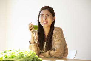 グリーンスムージーを持って笑っている女性の写真素材 [FYI04315957]