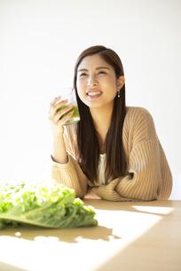 グリーンスムージーを持って笑っている女性の写真素材 [FYI04315958]