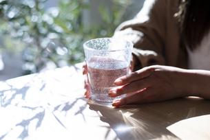 グラスに入った水を持っている手元の写真素材 [FYI04315962]