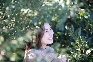 木々の中にいる笑顔の女性の写真素材 [FYI04315972]