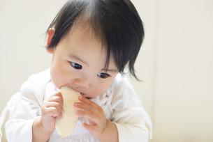 おせんべいを食べている赤ちゃんの写真素材 [FYI04315998]