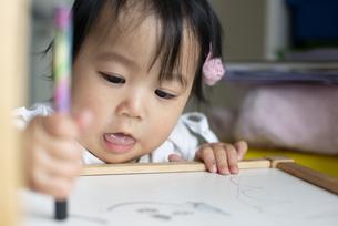 椅子に落書きをしている女の子の写真素材 [FYI04316008]