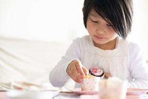 カップケーキにデコレーションしている女の子の写真素材 [FYI04316015]