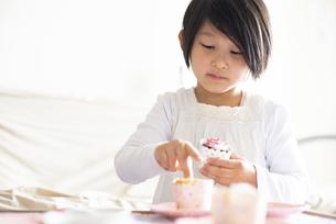 カップケーキにデコレーションしている女の子の写真素材 [FYI04316016]