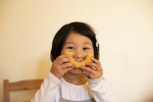 ドーナツを持ってポーズをしている女の子の写真素材 [FYI04316060]