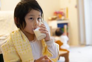 お風呂上がりに牛乳を飲んでいる女の子の写真素材 [FYI04316066]