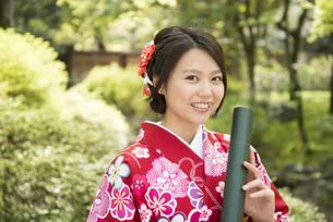 卒業証書の筒を持っている着物姿の女性の写真素材 [FYI04316111]