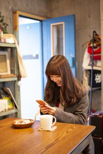 カフェでスマホを使って写真を撮っている女性の写真素材 [FYI04316123]