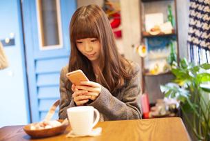 カフェでスマホを使って写真を撮っている女性の写真素材 [FYI04316124]