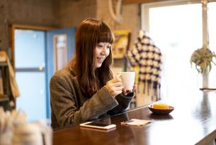 カフェのカウンターでコーヒーを飲んでいる女性の写真素材 [FYI04316125]