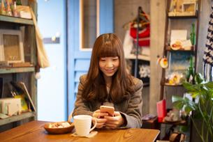 カフェでスマホを使って撮影をしている女性の写真素材 [FYI04316126]