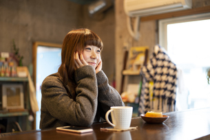 カフェのカウンターで頬杖をついている女性の写真素材 [FYI04316127]