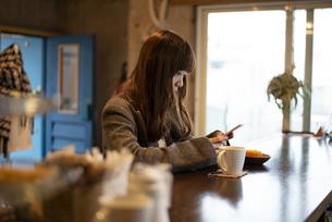 カフェのカウンターでスマホを触っている女性の写真素材 [FYI04316128]