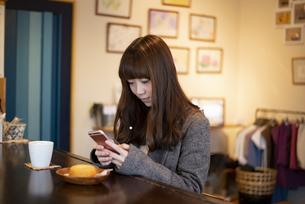カフェのカウンターでスマホを触っている女性の写真素材 [FYI04316129]