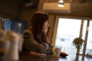 カフェのカウンターで遠くを見ている女性の写真素材 [FYI04316130]