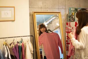 雑貨屋さんで服を選んでいる女性の写真素材 [FYI04316137]