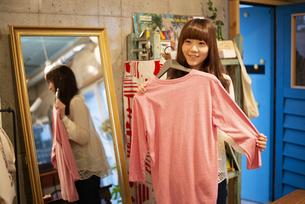 雑貨屋さんで服を選んでいる女性の写真素材 [FYI04316138]