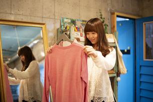 雑貨屋さんで服を選んでいる女性の写真素材 [FYI04316139]