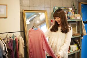 雑貨屋さんで服を選んでいる女性の写真素材 [FYI04316140]