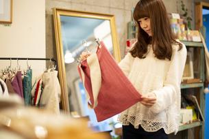 雑貨屋さんでカバンを選んでいる女性の写真素材 [FYI04316141]