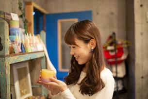 雑貨屋さんでキャンドルを選んでいる女性の写真素材 [FYI04316142]