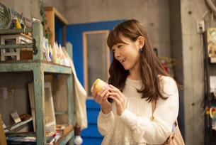 雑貨屋さんでキャンドルを選んでいる女性の写真素材 [FYI04316144]