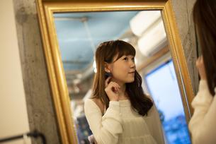 お店で鏡を見ている女性の写真素材 [FYI04316145]