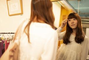 お店で鏡を見ている女性の写真素材 [FYI04316148]