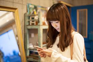 お店でスマホを見ている女性の写真素材 [FYI04316149]