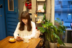 カフェでスマホを見ている女性の写真素材 [FYI04316154]