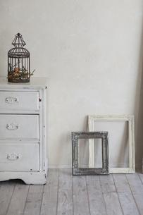 漆喰の壁の部屋にある額縁とチェストとドライフラワーの写真素材 [FYI04316314]