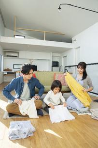 洗濯物をたたむ家族3人の写真素材 [FYI04316514]