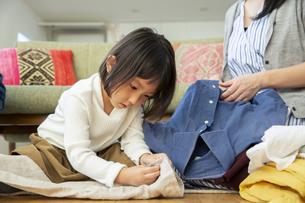 洗濯物をたたむ女の子の写真素材 [FYI04316517]
