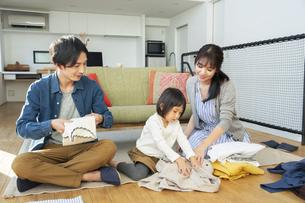 洗濯物をたたむ家族3人の写真素材 [FYI04316518]