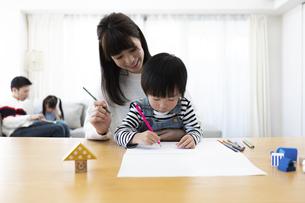 お絵描きする母息子と絵本を読む父娘の写真素材 [FYI04316940]