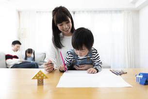 お絵描きする母息子と絵本を読む父娘の写真素材 [FYI04316941]