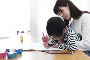 お絵描きする母息子と絵本を読む父娘の写真素材 [FYI04316943]