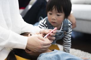 母親に歯磨きしてもらう女の子と見守る男の子の写真素材 [FYI04316965]