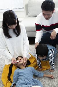 両親に歯磨きしてもらう子供たちの写真素材 [FYI04316971]