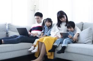 パソコンとタブレットを見る家族の写真素材 [FYI04316996]