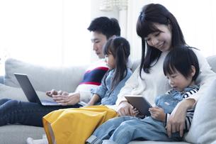 パソコンとタブレットを見る家族の写真素材 [FYI04316998]