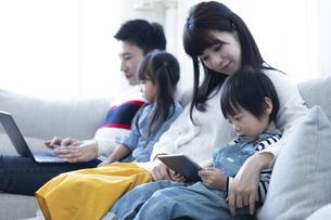 パソコンとタブレットを見る家族の写真素材 [FYI04316999]