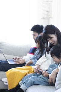 パソコンとタブレットを見る家族の写真素材 [FYI04317000]
