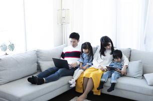 パソコンとタブレットを見る家族の写真素材 [FYI04317001]